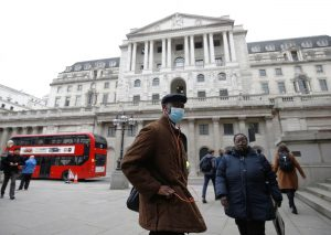 A man, wearing a protective face mask, walks in front of the Bank of England, following an outbreak of the coronavirus, in London