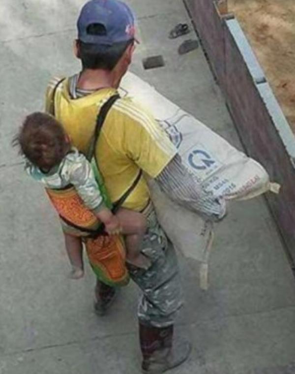Albañil carga a su bebé en la espalda mientras trabaja